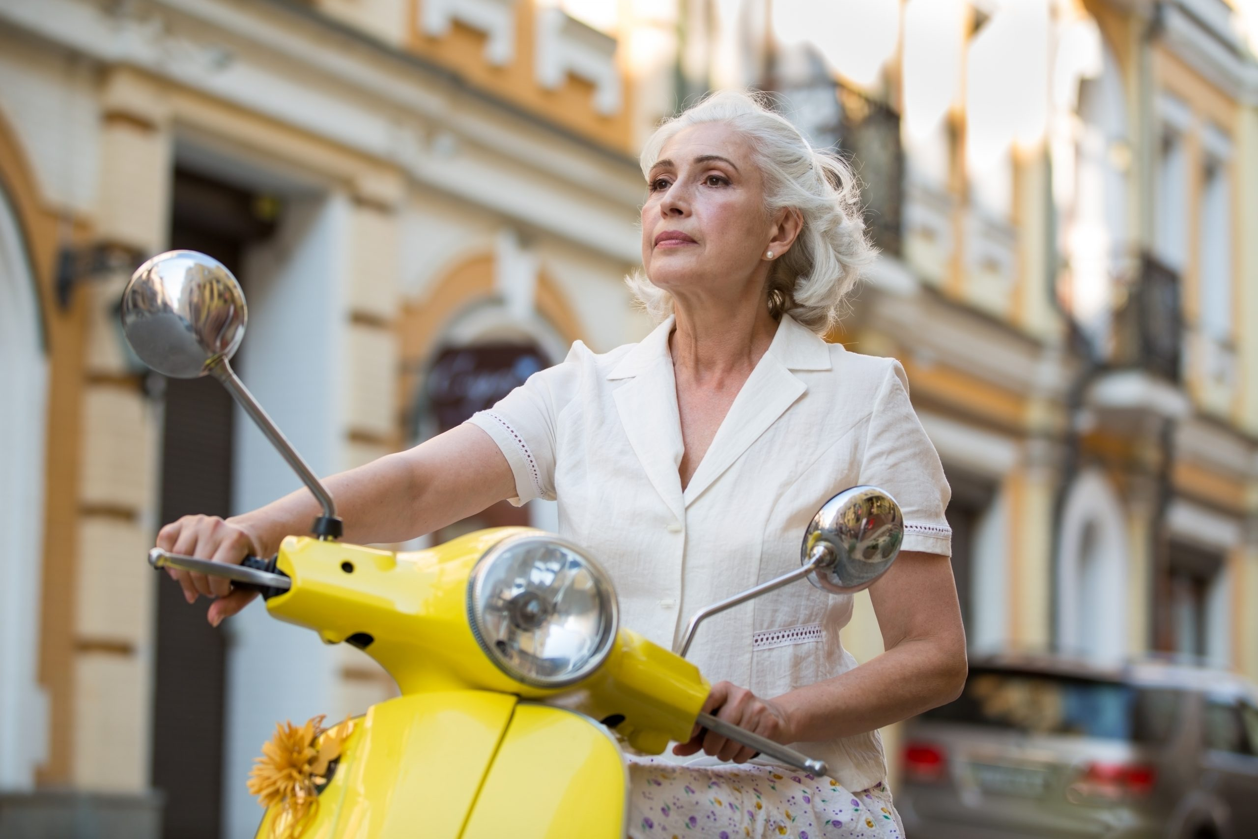 Mature white Woman on yellow scooter on SelfishMe Travel