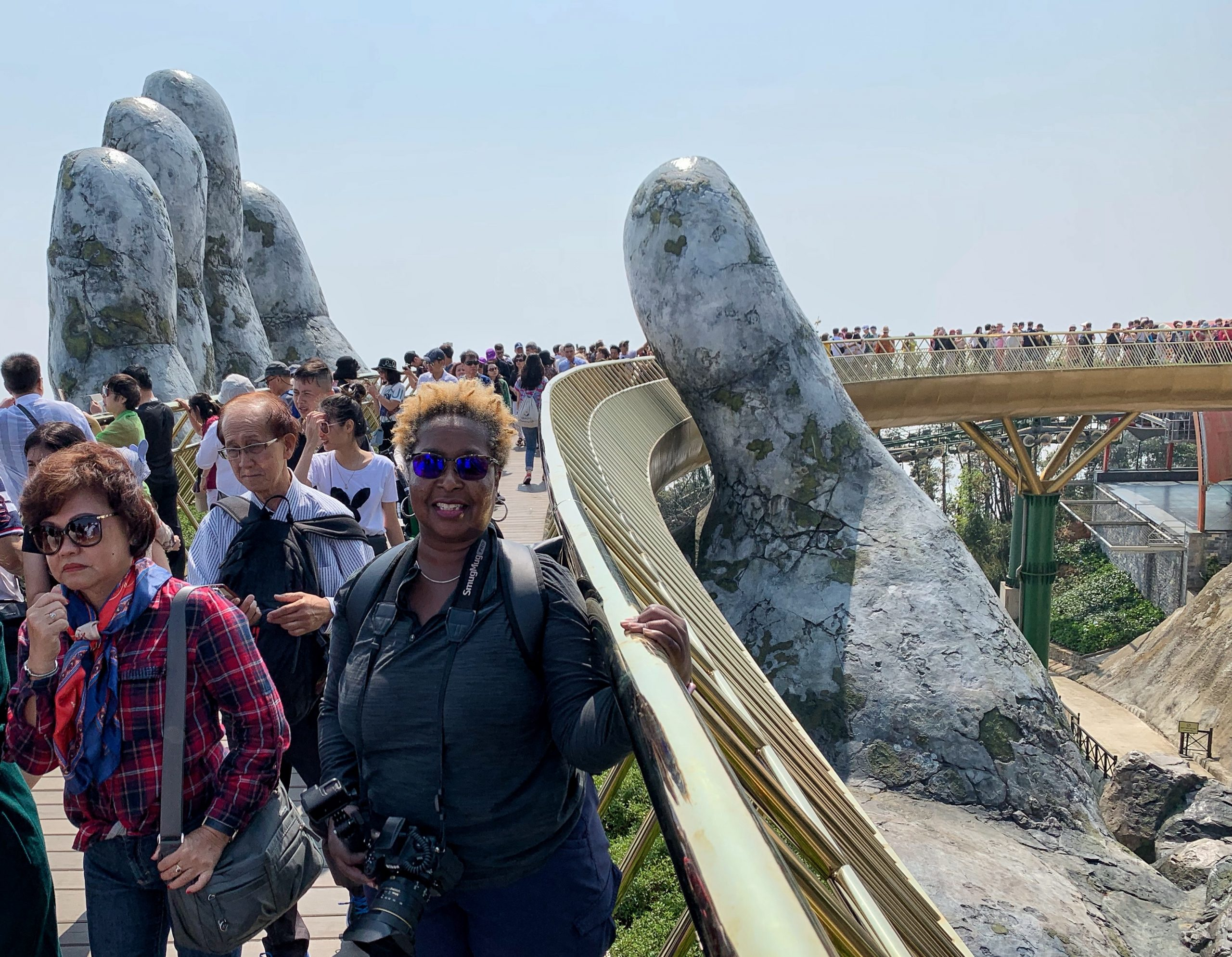 """Danielle Lewis, owner of SelfishMe Travel LLC, on the """"Hands of God"""" Golden Bridge at Sunworld's Ba Na Hills in Vietnam - image taken with an iPhone XS"""